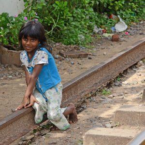 A girl sitting on the train tracks in Sri Lanka