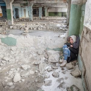 A Syrian girl sitting in the rubble of a ruined building