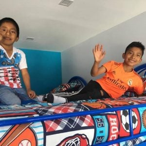 Two boys waving from a top bunk in the Guatemala protection home