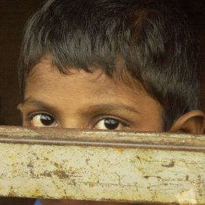A child peers over a barrier