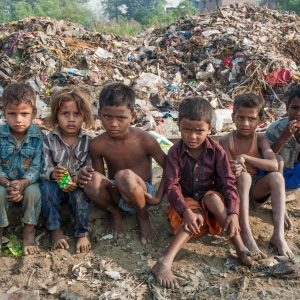 impoverished children sitting by littered roadside