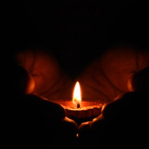 A candle burning in cupped hands