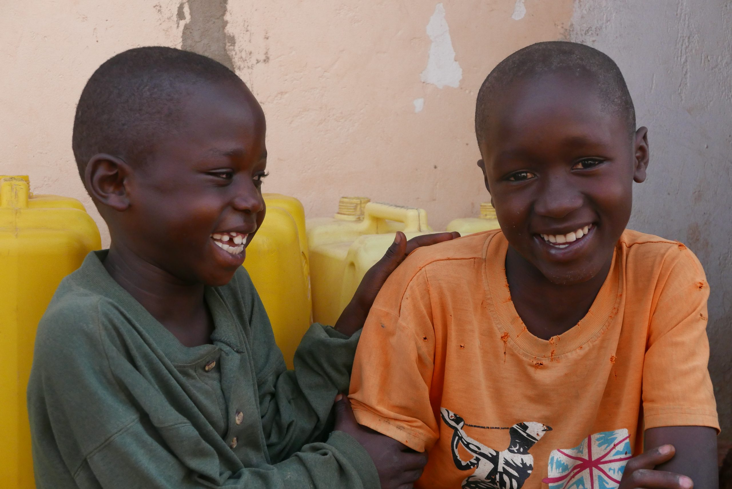 Two Ugandan children laughing together