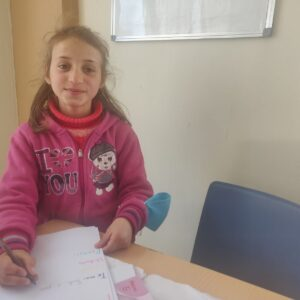 child writing at Global Care Albania's school club