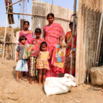 Family outside shack home in Patripul