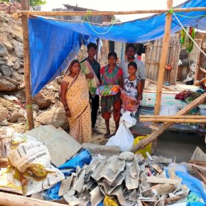Indian family standing in front of their shack, under a blue tarpaulin, hanging from a wooden frame, surrounded by rubble, holding a food gift from Global Care