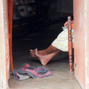 bare feet of Sri Lankan woman in darkened doorway of shack home